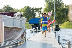 child running down dock toward pontoon